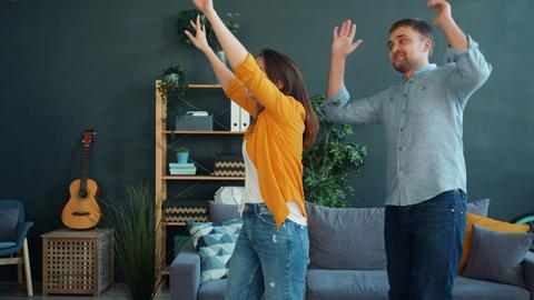 Joyful couple dancing at home having fun enjoying leisure time together Live Action