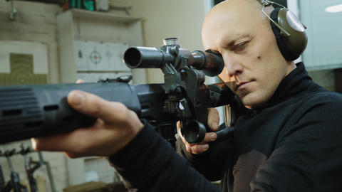 A man looks into the optical sight of a sniper rifle Live Action