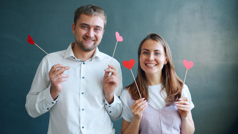 Slow motion of attractive people man and woman holding heart shape cards smiling Live Action