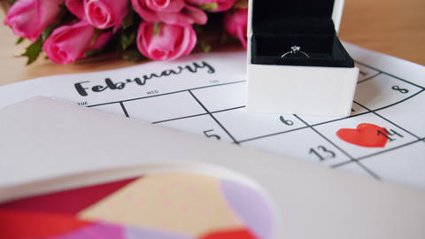 Beautiful celebration of Valentine's day with flowers, ring, card and calendar Live Action