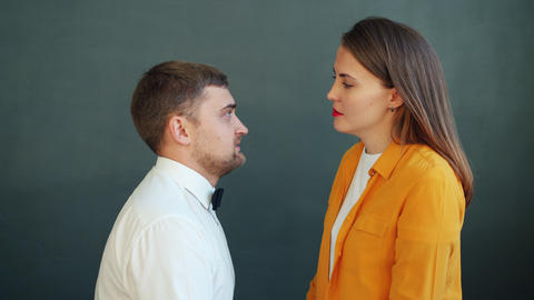 Portrait of couple kissing on gray background, girl leaving lipstick traces on Live Action