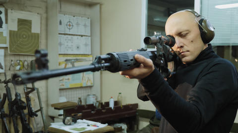 A man in headphones looks into the optical sight of a sniper rifle Live Action
