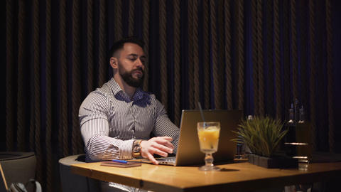 Bearded businessman working with laptop on new project, sitting alone on cofe Live Action