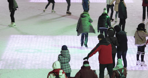 Skating rink visitors and stage and Christmas decoration on the background Live Action