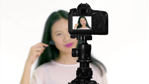 Asian teenager applying makeup with brush from behind camera vlogger concept Live Action