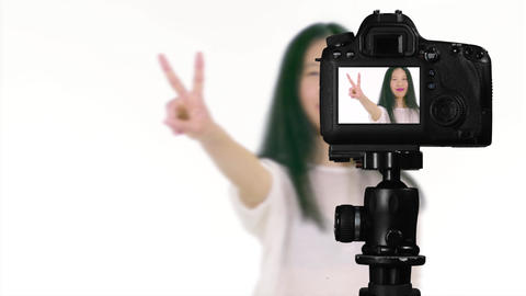 Asian teenager showing peace sign from behind camera vlogger concept Live Action