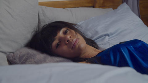 Annoyed woman with sleep disorder lying in bed Live Action