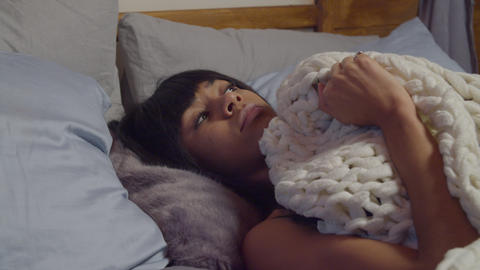 Scared woman peeking from duvet in fear at night Live Action