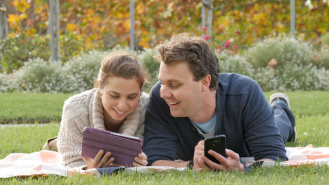Happy attractive young couple using mobile wireless technology devices Footage