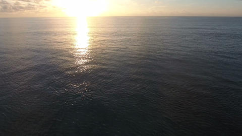 Flying drone shot of a sea surface with a beautiful sunset Footage