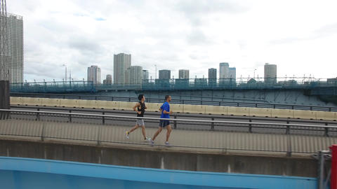 Caucasion and Japanese runner training on bridge Tokyo Drone aerial shot side vi ビデオ