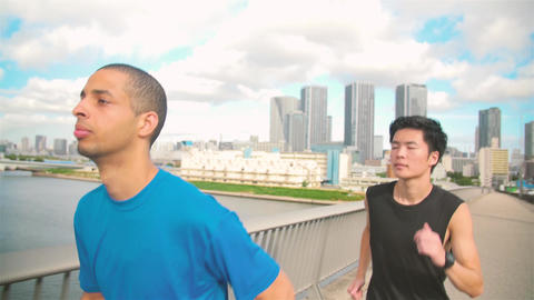 International and Japanese Runners training on Tokyo Bridge near Olympic grounds Footage