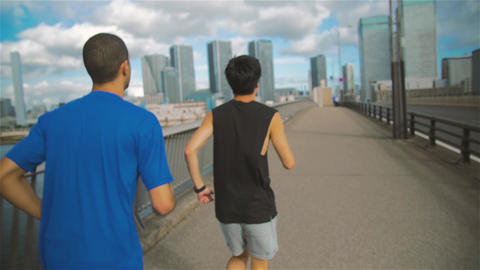 Japanese and International Runners steadycam follow shot Bridge city Tokyo Backg Footage