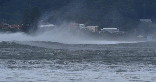 Sea spray form massive waves that are braking along coastal town Footage