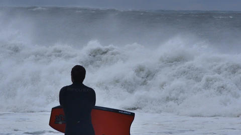 NSW, AUSTRALIA - JUNE 2016: bodyboarder surfer looking at stormy sea waves Footage