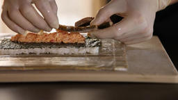 Close-up of Sushi Chef Hands puts smoked eel on a nori leaf and crab meat Live Action