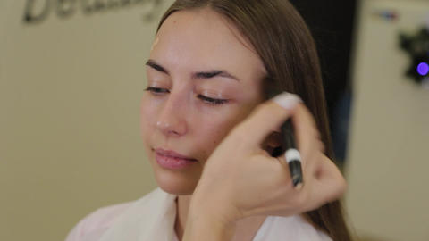 Professional make-up artist applies foundation cream on client's face with brush Live Action