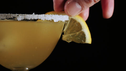 Bartender assembles a lemon slice on a classic yellow cocktail drink Live Action