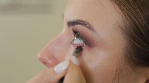Professional makeup artist puts eye shadow on a client of a beauty salon Live Action