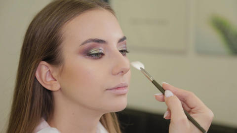 Professional makeup artist does makeup to a client of a beauty salon Live Action