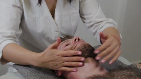 Professional woman masseur makes lymphatic massage to a man. Facial and cervical Live Action
