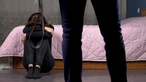 A young woman with bruises on her face sits on the floor and cries. A young man Live Action