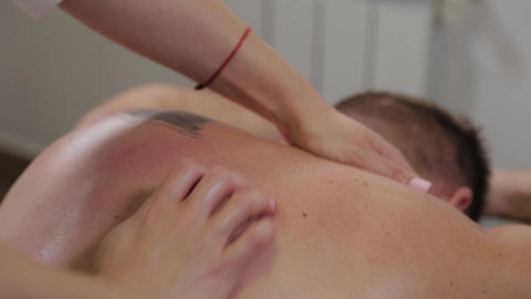 Professional woman masseur doing massage on the back of a man. Massage at the Live Action