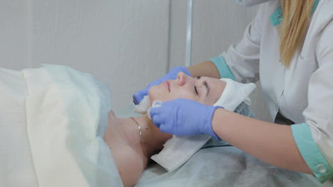 Professional beautician woman rubs her face before the procedure with wet wipes Live Action