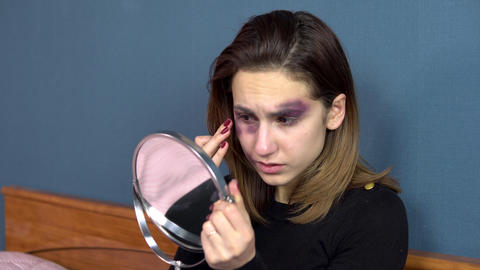 A young woman examines bruises on her face in the mirror. Quarrels in a young Live Action