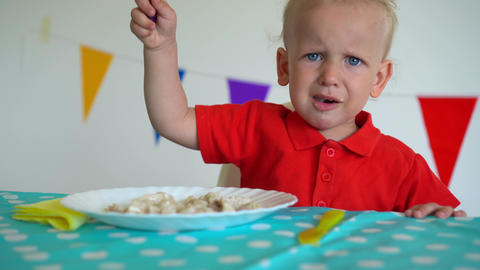 Upset toddler child boy sitting by table and eating dumplings. Gimbal movement Live Action