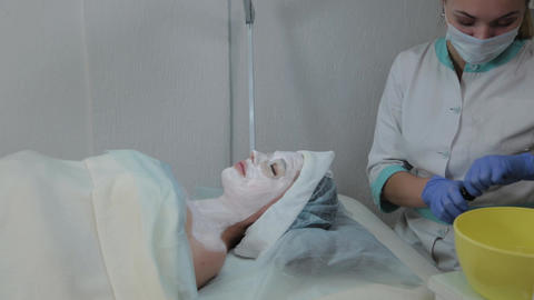 Beautiful woman lies with a mask on her face in a beauty salon Live Action
