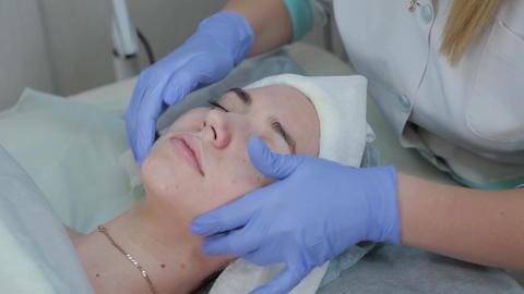 Professional beautician woman massaging client's face Live Action