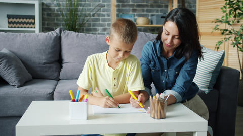 Small boy drawing with markers together with caring mother in cozy room at home Live Action
