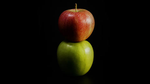 Organic green and red apple rotates against black background Live Action
