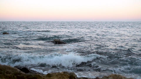Waves on the Mediterranean Sea. Waves hit the rocks at pink sunset. Slow motion Live Action