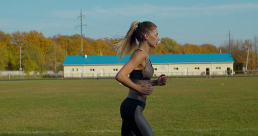 Woman running at a stadium in sunny day Live Action