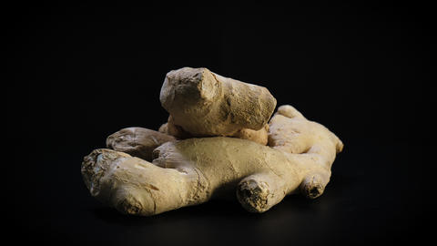 Fresh organic ginger rotates against black background Live Action