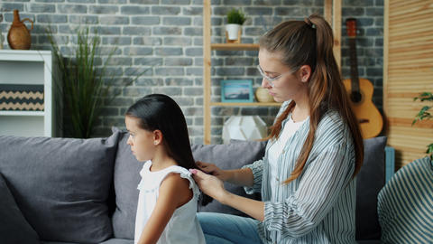 Caring mother is brushing daughter's hair taking care of beautiful child at home Live Action