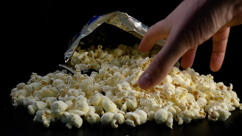 One hand picks popcorn from a bag against black background Live Action