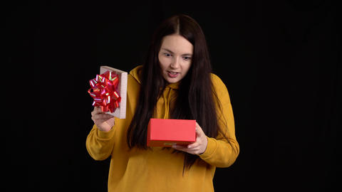 Young woman with a gift box on black background. gift box... Stock Video Footage