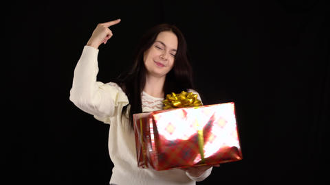 Young woman with a gift box on black background. gift box with white ribbon for Live Action