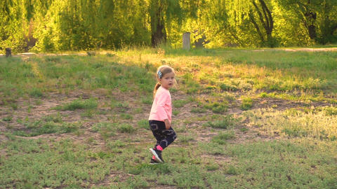 Little happy girl running outdoor in the park in slow motion Live Action