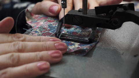 A sewing machine sews and moves the fabric. A woman puts fabric in a sewing Live Action