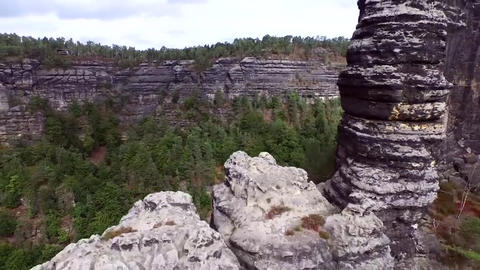 Rocks in the Czech Republic. Sunshine. White, gray, thick clouds are visible in Live Action