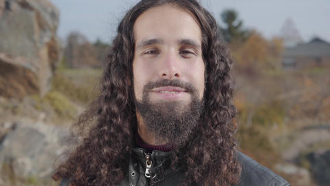Close-up face of handsome Middle Eastern man with long black hair and beard Live Action
