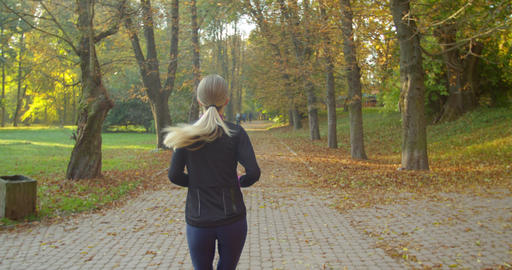 Woman Running in the Sunny City Park. Morning Light Live Action