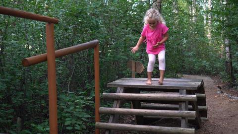 Barefoot little girl walk through wooden logs bridge. Foot massage path Live Action