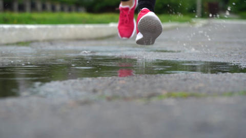 Legs of a runner in sneakers. Sports woman jogging outdoors, stepping into muddy Live Action