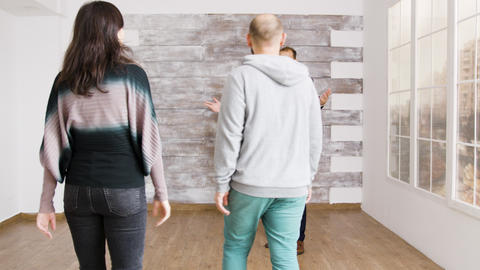 Real estate agent shows new apartment to young couple Live Action