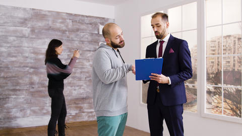 Real estate agent in business suit describes apartment to client Live Action